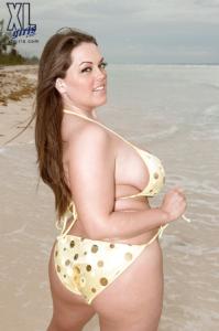 Plus sized bikini model on the beach, wearing a yellow bikini, smiling over bare shoulder