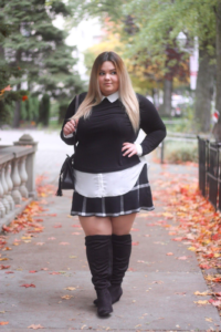 Full figured blonde with hand on hip wearing black sweater, skirt and tall boots on the sidewalk in autumn.