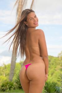 Topless bikini model in thong smiling over bare shoulder