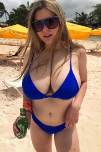 Large breasted beach babe cleavage spilling out of