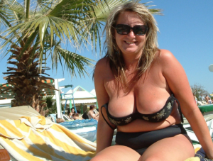 Smiling mature chubby blonde smiling in black bikini by the pool.