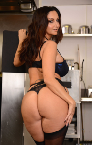 mature brunette Ava Addams with long dark hair standing in black and blue lingerie in a restaurant kitchen, looking over bare shoulder.