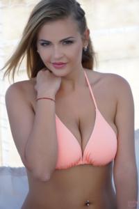 Beautiful bikini model in peach bikini looking into the camera.