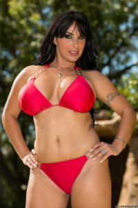 Mature dark haired bikini model in red standing with hands on hips.
