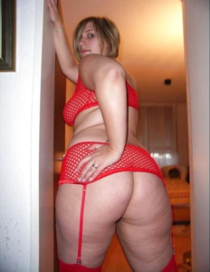 Chubby blonde woman with big butt standing in doorway blonde hair in face looking back over bare shoulder wearing red lingerie.