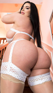 Curvy lingerie model with long dark hair and big round butt looking over bare shoulder.