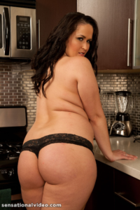 Plus sized brunette Carmella in black panties standing in kitchen looking over bare shoulder.