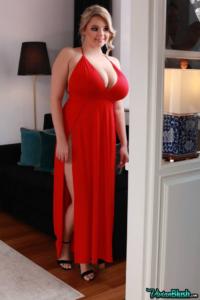 Blonde model Vivian smiling, standing, wearing a open shoulder low cut red dress.