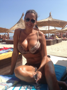 Large breasts in bikini on beach with pretty smile and big sunglasses.