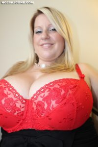 Chubby mature blonde with breasts spilling out of bra at an up angle.
