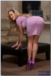 Mature curvy blonde standing bent over, smiling over shoulder. Wearing a tight fitting lilac dress and high heels.
