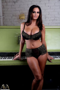 Ava Adam's in black bra and panty set standing in front of upright piano.