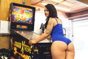 Full figured swimsuit model with long dark hair. Playing pinball, looking over bare shoulder.