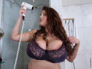 Sexy Curvy Eden Mor spilling out of purple bra cleavage.