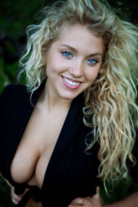 blonde with a pretty smile, blue eyes and low cut cleavage.