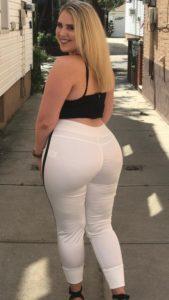 Curvy blonde in tight white pants and black bra halter smiling over bare shoulder