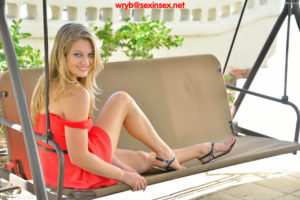 Sexy blonde Veronica sitting on porch swing smiling over bare shoulder.